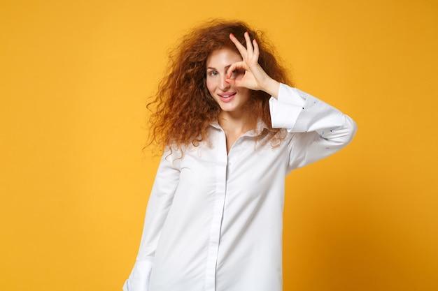 Młoda ruda kobieta dziewczyna w dorywczo białej koszuli pozuje odizolowana na żółto pomarańczowej ścianie