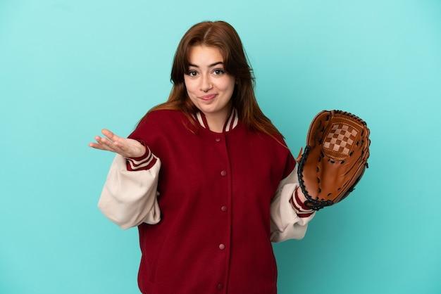 Młoda ruda kobieta gra w baseball na białym tle na niebieskim tle, mając wątpliwości podczas podnoszenia rąk
