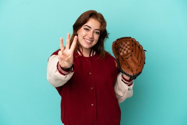 Młoda ruda kobieta gra w baseball na białym tle na niebieskim tle szczęśliwa i liczy trzy palcami
