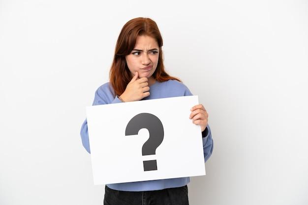 Młoda ruda kobieta na białym tle trzyma afisz z symbolem znaku zapytania i myśleniem