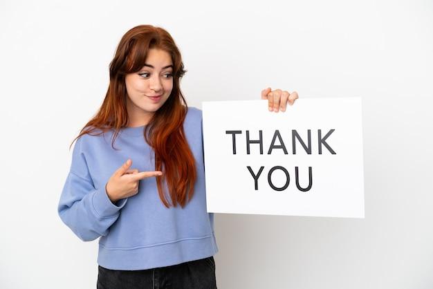 Młoda ruda kobieta na białym tle trzyma afisz z tekstem dziękuję i wskazując go