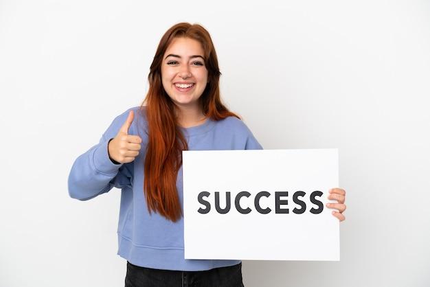 Młoda ruda kobieta na białym tle trzyma afisz z tekstem sukces z kciukiem do góry