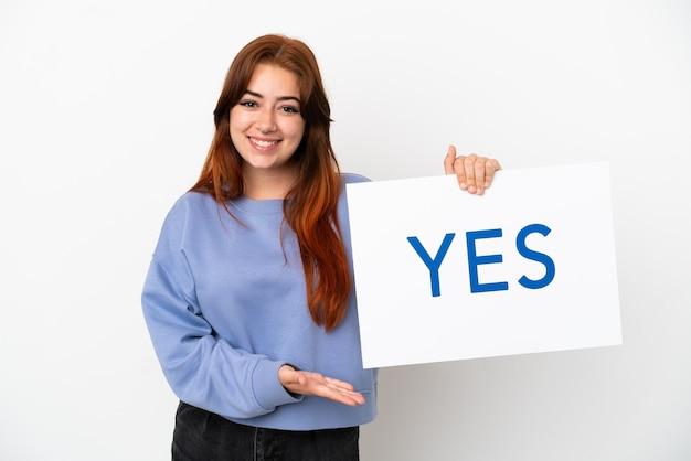 Młoda ruda kobieta na białym tle trzyma afisz z tekstem tak ze szczęśliwym wyrazem