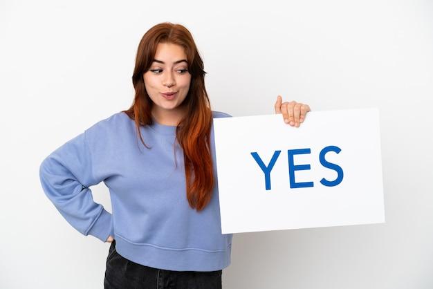 Młoda ruda kobieta na białym tle trzyma afisz z tekstem tak