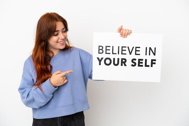 """Młoda ruda kobieta na białym tle trzyma afisz z tekstem """"uwierz w siebie"""" i wskazując go"""