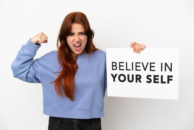 Młoda ruda kobieta na białym tle trzyma afisz z tekstem wierz w siebie i robi silny gest