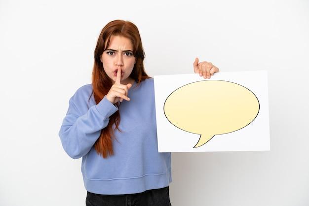 Młoda ruda kobieta na białym tle trzymająca afisz z ikoną dymka robi gest ciszy