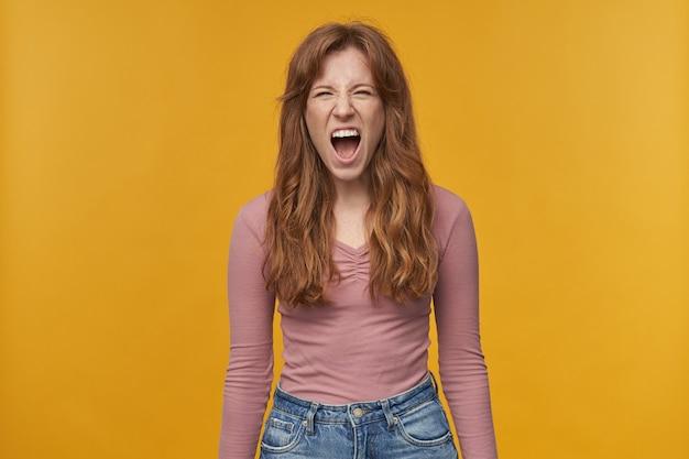Młoda ruda kobieta z falującymi włosami i piegami, krzycząca i krzycząca z szeroko otwartymi ustami i negatywnym wyrazem twarzy na żółto