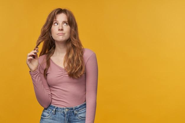 Młoda ruda kobieta, z falującymi włosami i piegami ma sny lub myśli na żółto