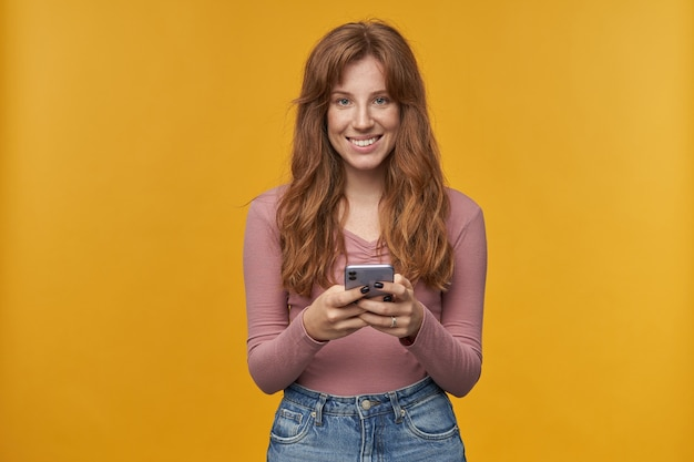Młoda ruda kobieta z piegami, trzymająca telefon obiema rękami podczas pisania wiadomości i uśmiechająca się
