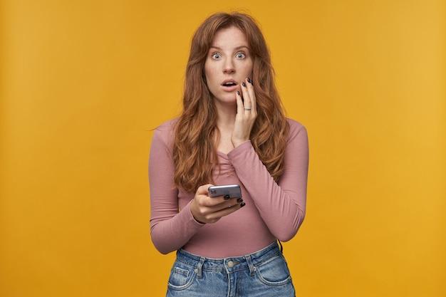 Młoda, ruda kobieta z piegami zdumiona wyrazem twarzy trzymając telefon