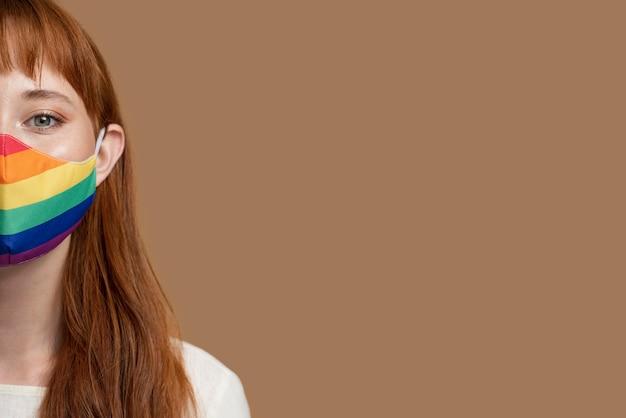 Młoda ruda kobieta z tęczową medyczną maską