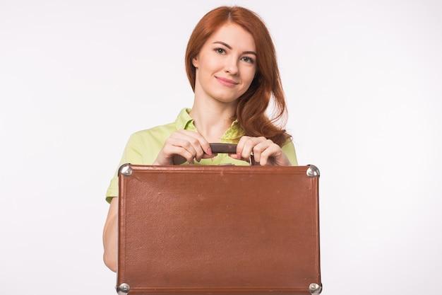 Młoda ruda kobieta ze skórzaną walizką vintage na białym tle.