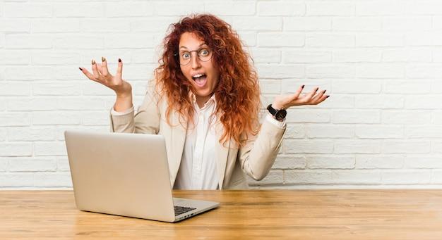 Młoda ruda kręcona kobieta pracująca z laptopem świętująca zwycięstwo lub sukces, jest zaskoczony i zszokowany.