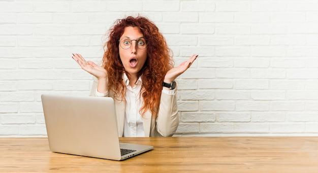 Młoda ruda kręcona kobieta pracująca z laptopem zaskoczona i zszokowana.