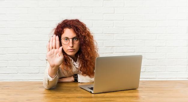 Młoda ruda kręcona kobieta pracuje z jej laptopa stojąc z wyciągniętą ręką pokazując znak stopu, uniemożliwiając ci.