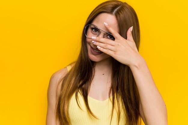 Młoda ruda rudowłosa kobieta z piegami mruga przez palce, zakłopotana zakrywająca twarz.