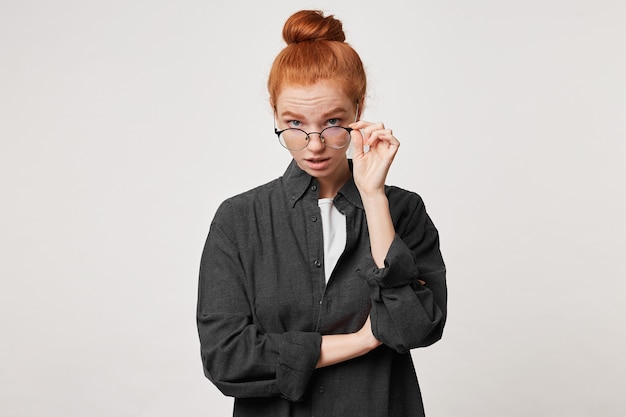 Młoda rudowłosa dziewczyna ubrana w czarną męską koszulę patrzy w kamerę