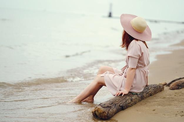 Młoda rudowłosa dziewczyna w dużym okrągłym kapeluszu i różowej sukience siedzi na plaży w pobliżu oceanu