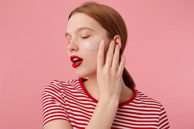 Młoda rudowłosa dziewczyna z czerwonymi ustami i łatami pod oczami, ubrana w czerwoną koszulkę w paski, dotyka policzka, stoi z zamkniętymi oczami, ciesząc się wolnym czasem na pielęgnację skóry.