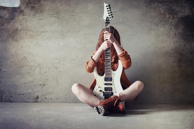 Młoda rudowłosa dziewczyna z gitarą elektryczną. muzyk rockowy dziewczyna w skórzanej kurtce. jest ładną piosenkarką i wykonawcą muzyki rockowej.