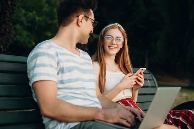 Młoda rudowłosa dziewczyna z piegami za pomocą smartfona, patrząc na swojego chłopaka. dwóch młodych studentów siedzi na ławce.