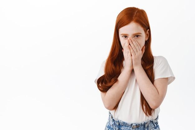 Młoda rudowłosa dziewczyna zakrywa twarz i wygląda na zaskoczoną z przodu, dysząc z zaskoczeniem