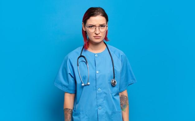Młoda rudowłosa kobieta czuje się smutna, zdenerwowana lub zła i patrzy w bok z negatywnym nastawieniem, marszcząc brwi z powodu sprzeciwu. koncepcja pielęgniarki szpitalnej