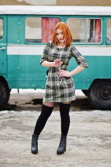 Młoda rudowłosa kobieta dama z telefonem komórkowym i słuchawkami, ubrana w kraciastą sukienkę w starym autobusie minivana w stylu vintage.