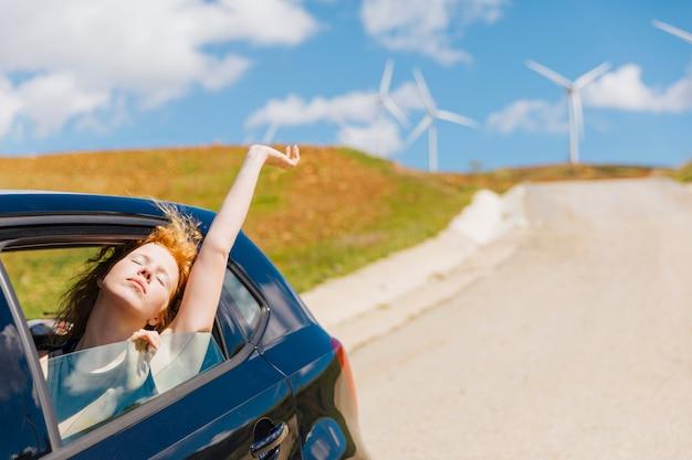 Młoda rudowłosa kobieta kochająca życie z okna samochodu
