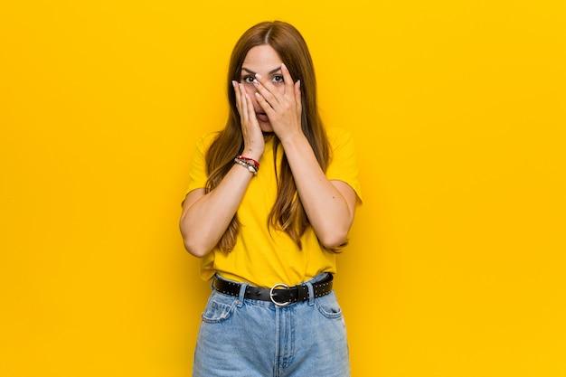 Młoda rudowłosa kobieta mruga przez palce przestraszona i zdenerwowana.