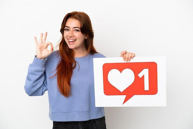 Młoda rudowłosa kobieta na białym tle trzyma afisz z ikoną like i świętuje zwycięstwo