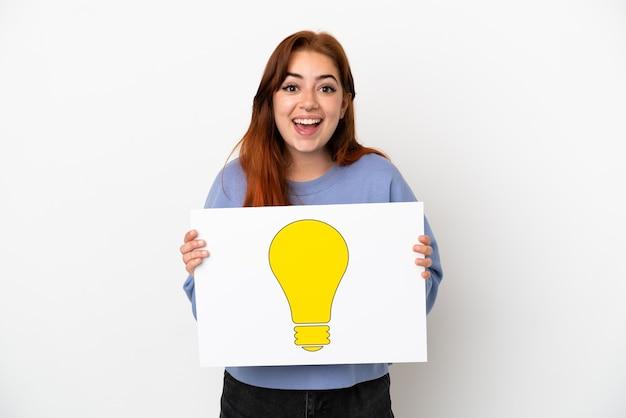 Młoda rudowłosa kobieta na białym tle trzyma afisz z ikoną żarówki z szczęśliwym wyrazem twarzy