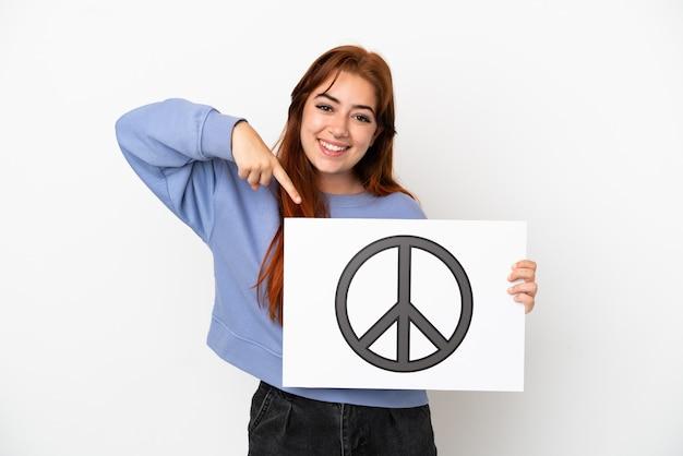 Młoda rudowłosa kobieta na białym tle trzyma afisz z symbolem pokoju i wskazuje go