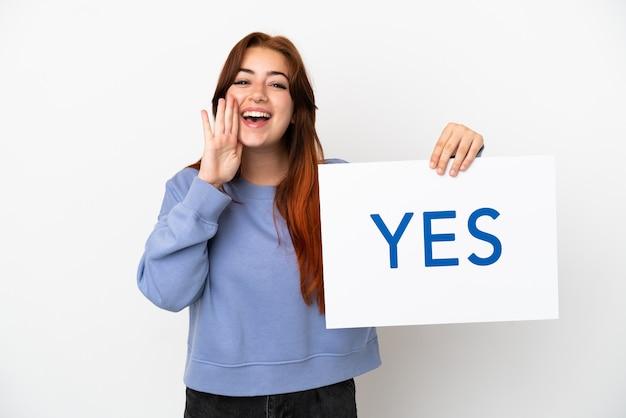 Młoda rudowłosa kobieta na białym tle trzyma afisz z tekstem tak i krzyczy