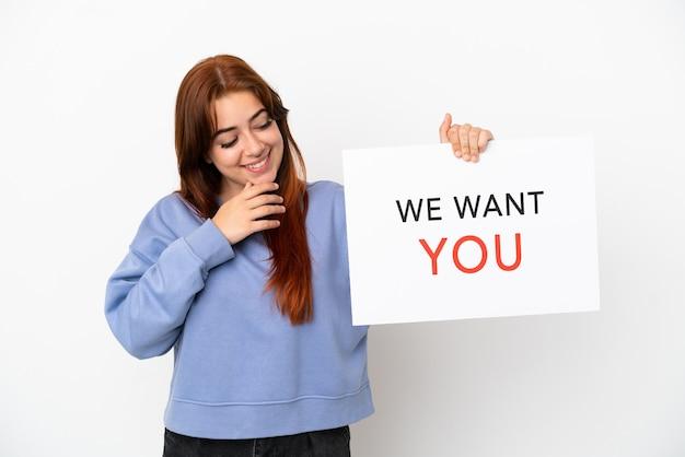 Młoda rudowłosa kobieta na białym tle trzyma deskę we want you ze szczęśliwym wyrazem twarzy