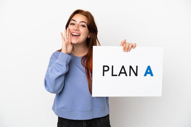 Młoda rudowłosa kobieta na białym tle trzyma plakat z napisem plan a i krzyczy