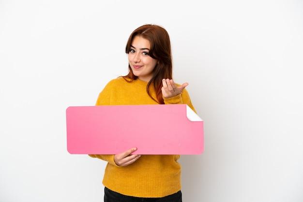 Młoda rudowłosa kobieta na białym tle trzyma pustą afisz i robi nadchodzący gest