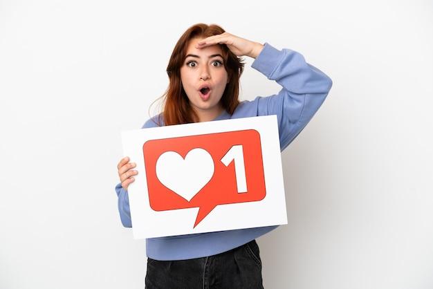 Młoda rudowłosa kobieta na białym tle trzymająca afisz z ikoną like z zaskoczonym wyrazem twarzy