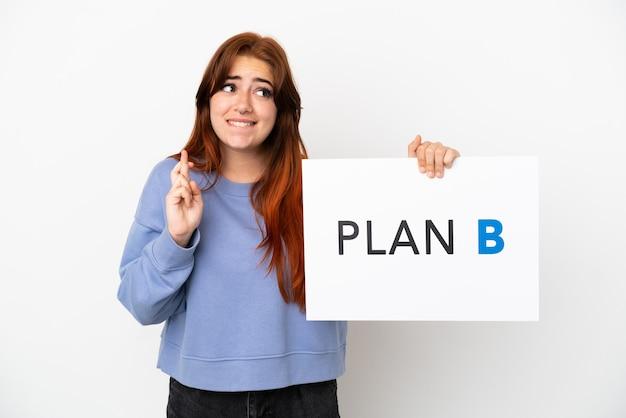 Młoda rudowłosa kobieta na białym tle trzymająca afisz z napisem plan b ze skrzyżowanymi palcami