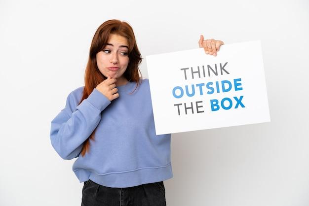 Młoda rudowłosa kobieta na białym tle trzymająca afisz z tekstem think outside the box and thinking