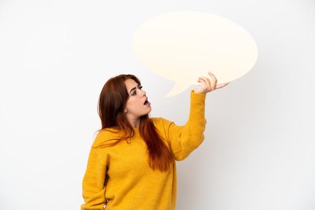 Młoda rudowłosa kobieta na białym tle trzymająca pusty dymek