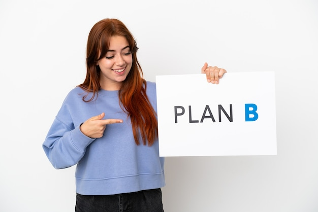 Młoda rudowłosa kobieta na białym tle trzymająca tabliczkę z napisem plan b