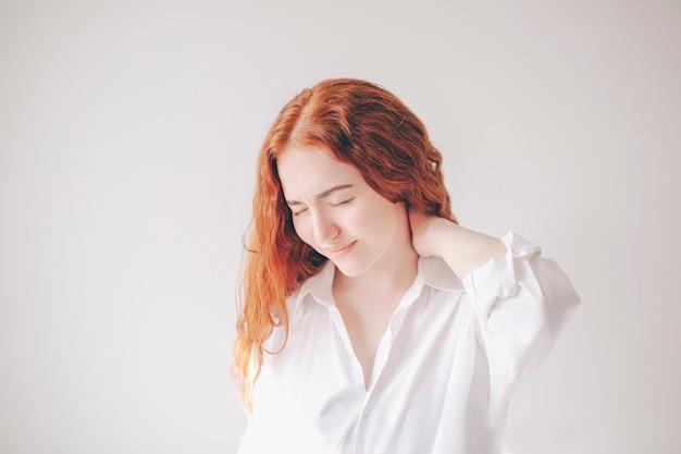 Młoda, rudowłosa kobieta na białym tle w białej koszulce ma ból szyi