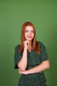 Młoda rudowłosa kobieta na zielonej ścianie przemyślane przesłuchanie