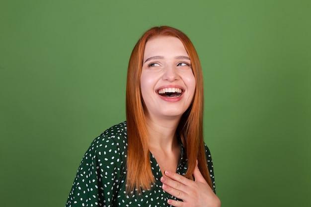 Młoda rudowłosa kobieta na zielonej ścianie uśmiecha się i śmieje, w dobrym nastroju, pozytywnych emocjach