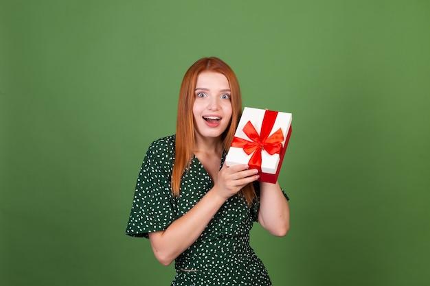 Młoda rudowłosa kobieta na zielonej ścianie z pudełkiem na prezenty szczęśliwa podekscytowana zdumiona zdziwiona