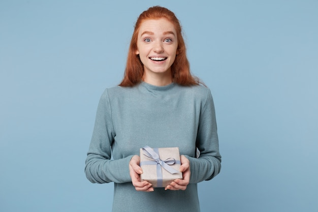 Młoda rudowłosa kobieta otrzymała zapakowany prezent przewiązany niebieską wstążką, trzymając go w dłoniach z uśmiechem