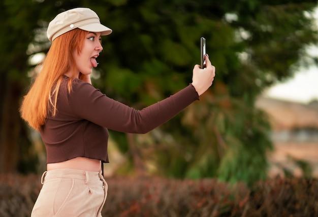 Młoda rudowłosa kobieta rasy kaukaskiej robi selfie ze śmieszną miną