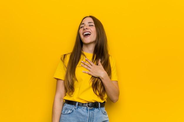 Młoda rudowłosa kobieta śmieje się głośno, trzymając rękę na piersi.